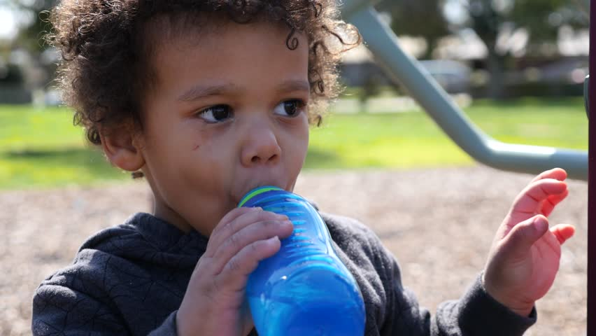Sad, crying male child drinking from a water bottle | Shutterstock HD Video #30771640
