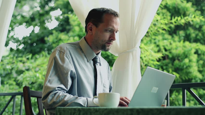 Businessman with cellphone and laptop computer working on his balcony  | Shutterstock HD Video #3078805