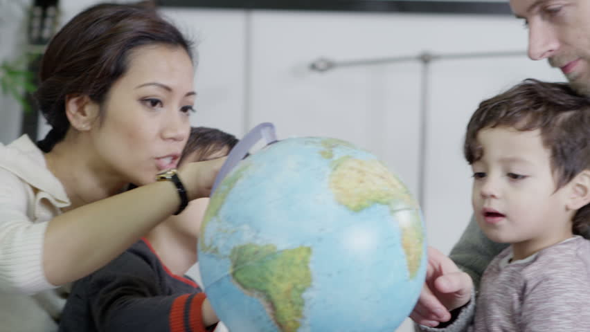 An attractive mixed ethnicity couple are educating their young two young sons at home and using a globe to teach them about the world. In slow motion. | Shutterstock HD Video #3081322