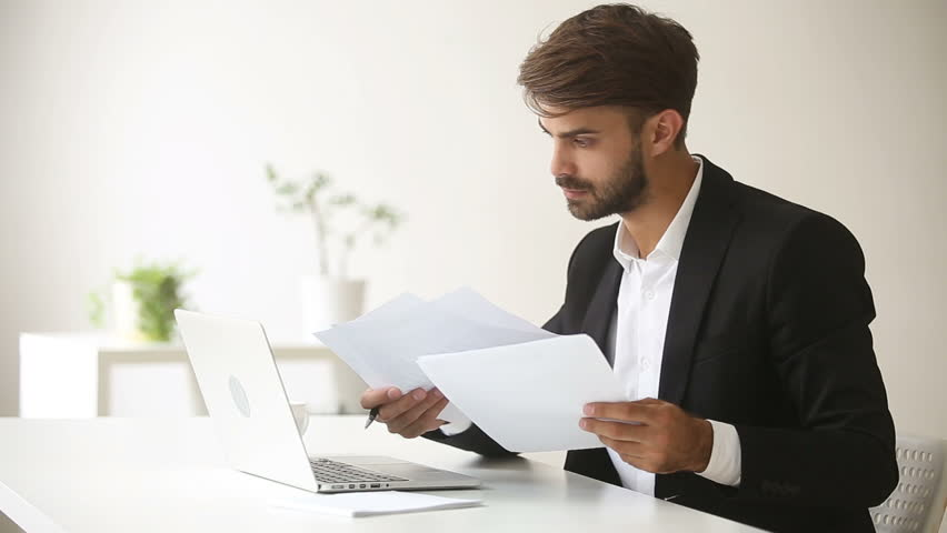 Young businessman wearing suit working with laptop documents sitting at office desk, financial analyst using accounting business app, economist analyzing statistics, trader smiling looking at camera | Shutterstock HD Video #30832636