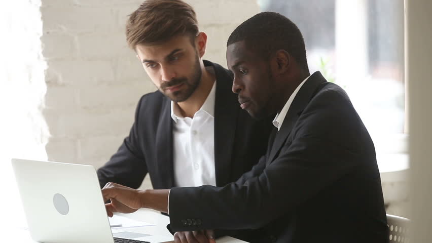 African american businessman showing computer presentation to caucasian client sitting at office desk, explaining new project business plan with pc at meeting, diverse partners negotiate using laptop