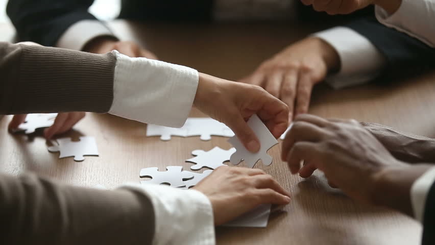 Close up view of business people hands trying to connect assembling jigsaw puzzle and join pieces on conference table in office, team help and support, finding right solutions in teamwork concept