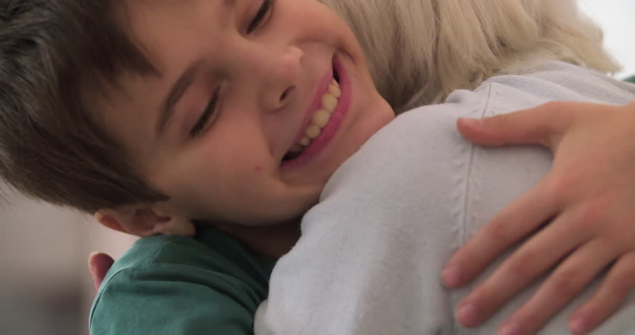 Grandson kid hugging grandmother at home HD slow-motion video. Child boy running to old woman. Close-up of smiling face. Grandparents and grandchildren love