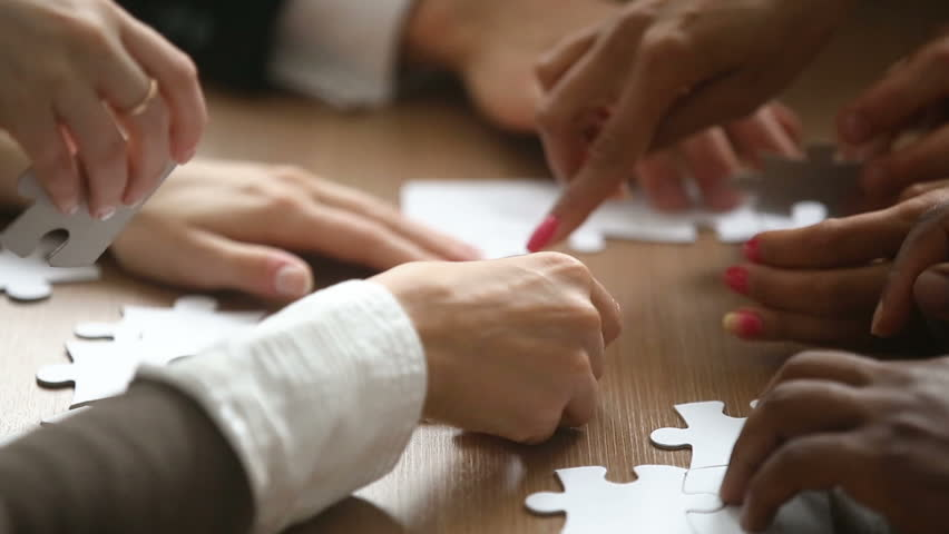 Close up view of hands assembling jigsaw puzzle on table, group of business people matching pieces playing board game, right decision making in business, help and support in teamwork concept Royalty-Free Stock Footage #30848638