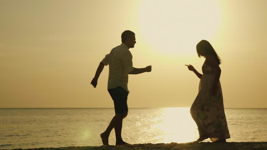 Silhouettes of young people dancing happily on the beach