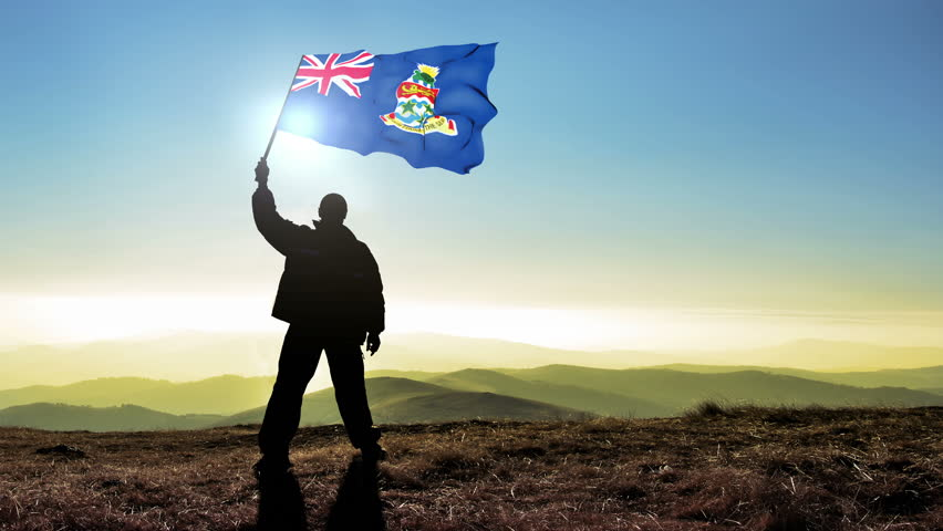 Successful silhouette man winner waving Cayman Islands flag on top of the mountain peak. Cinemagraph LOOP background