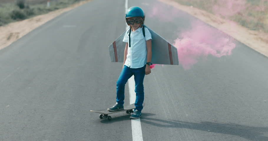 CINEMAGRAPH - seamless loop. Little boy wearing helmet and styrofoam wings standing on a skateboard on a rural road, pretending to be a pilot #30858529