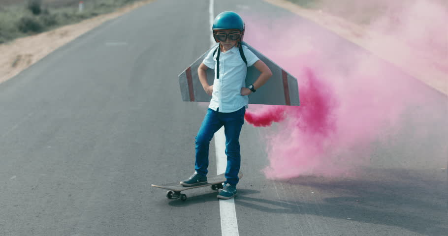 CINEMAGRAPH - seamless loop. Little boy wearing helmet and styrofoam wings standing on a skateboard on a rural road, pretending to be a pilot #30860722