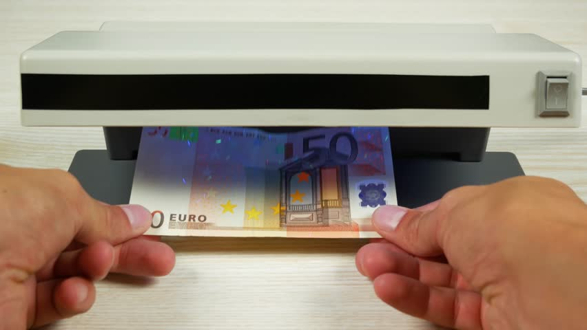 Authentication of money on the detector. Banknote denomination of 50 euros under the lamp of the detector. | Shutterstock HD Video #30863416