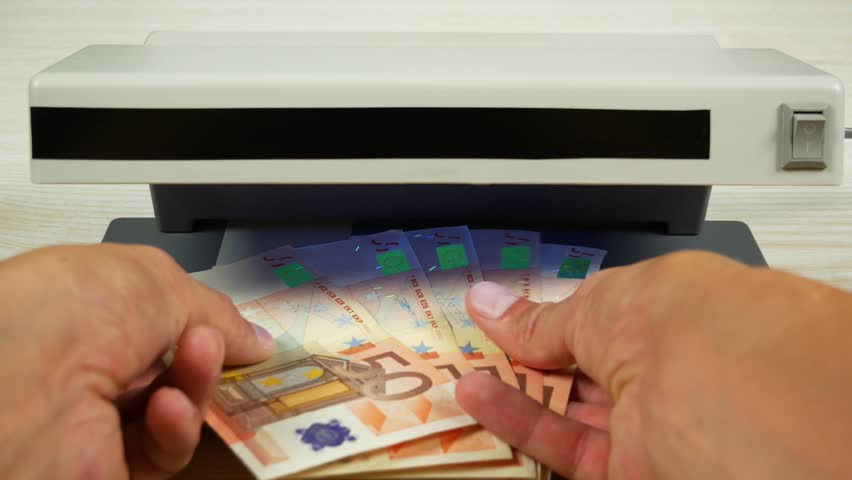 A few euro notes in hand. Check on the currency detector. | Shutterstock HD Video #30863842
