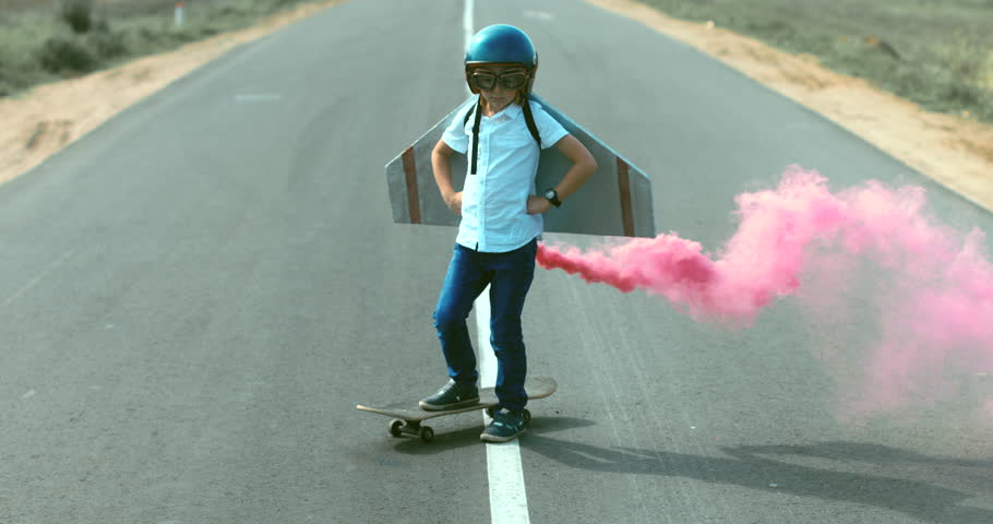 Little boy wearing helmet and styrofoam wings standing on a skateboard on a rural road, pretending to be a pilot. 4K UHD RAW edited footage #30869167
