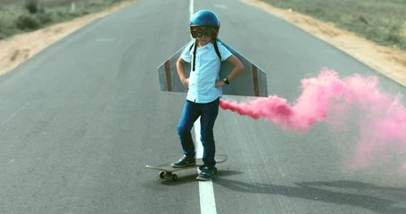 Little boy wearing helmet and styrofoam wings standing on a skateboard on a rural road, pretending to be a pilot. 4K UHD RAW edited footage