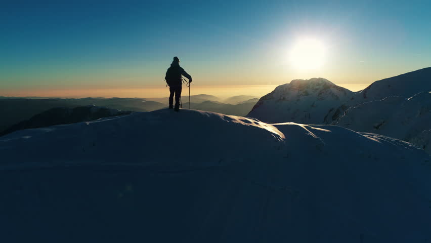 Aerial - Adult male mountaineer standing on top of snowy mountain top and holding his hand on his forehead, looking into the distance | Shutterstock HD Video #30874273