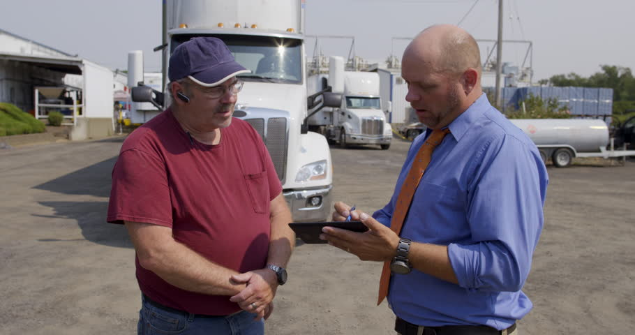 Truck driver talks to official, insurance agent or delivery manager, in shirt and tie who asks him to sign an electronic notepad. Medium shot in front of parked white truck on summer day. 4K