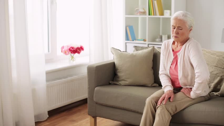 old age, health problem and people concept - senior woman suffering from pain in leg at home