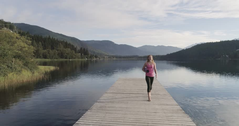 Beautiful Young Woman Walking On A Dock With A Yoga Mat  #30906346