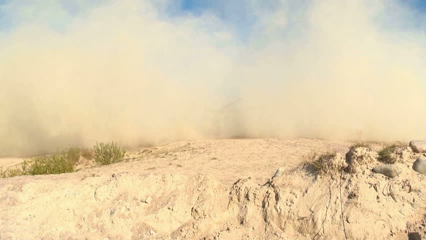 Dust rises when a helicopter lands in the desert, clouds of sand fly into the air and move.