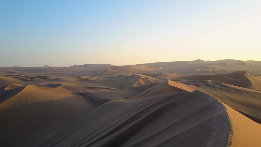 Aerial drone footage on a sunny day above sand dunes of Peru. Close to Ica and Huacachina. Similar to Sahara and Emirates Deserts. Boogie cars driving and people sandboarding. Color Corrected.   Shutterstock HD Video #30910480