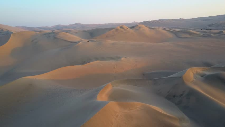 Aerial drone footage on a sunny day above sand dunes of Peru. Close to Ica and Huacachina. Similar to Sahara and Emirates Deserts. Boogie cars driving and people sandboarding. Color Corrected.   Shutterstock HD Video #30910489