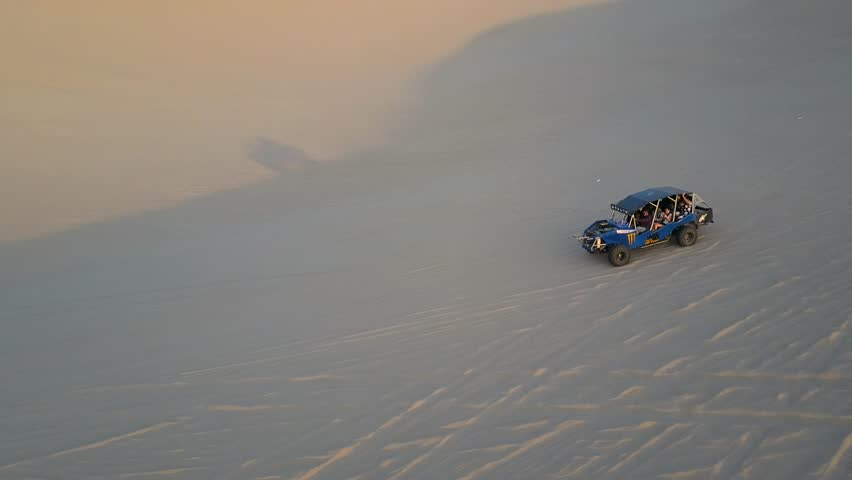 Aerial drone footage on a sunny day above sand dunes of Peru. Close to Ica and Huacachina. Similar to Sahara and Emirates Deserts. Boogie cars driving and people sandboarding. Oasis nearby.   Shutterstock HD Video #30910501