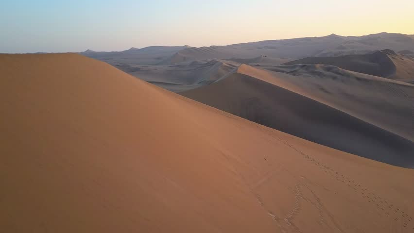 Aerial drone footage on a sunny day above sand dunes of Peru. Close to Ica and Huacachina. Similar to Sahara and Emirates Deserts. Boogie cars driving and people sandboarding. Oasis nearby.