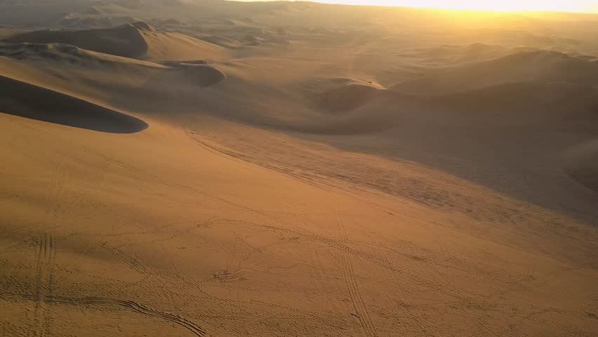Aerial drone footage on a sunny day above sand dunes of Peru. Close to Ica and Huacachina. Similar to Sahara and Emirates Deserts. Boogie cars driving and people sandboarding. Color Corrected.   Shutterstock HD Video #30910510