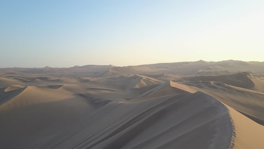 Aerial drone footage on a sunny day above sand dunes of Peru. Close to Ica and Huacachina. Similar to Sahara and Emirates Deserts. Boogie cars driving and people sandboarding. Oasis nearby.   Shutterstock HD Video #30910534