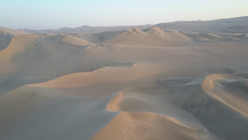 Aerial drone footage on a sunny day above sand dunes of Peru. Close to Ica and Huacachina. Similar to Sahara and Emirates Deserts. Boogie cars driving and people sandboarding. Oasis nearby.   Shutterstock HD Video #30910543