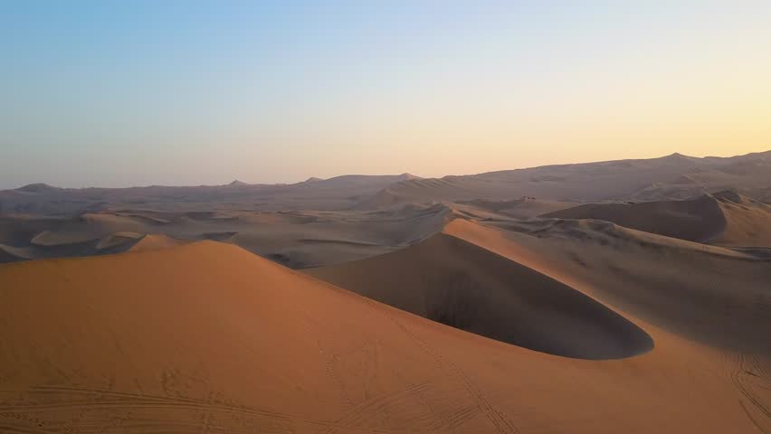 Aerial drone footage on a sunny day above sand dunes of Peru. Close to Ica and Huacachina. Similar to Sahara and Emirates Deserts. Boogie cars driving and people sandboarding. Color Corrected.