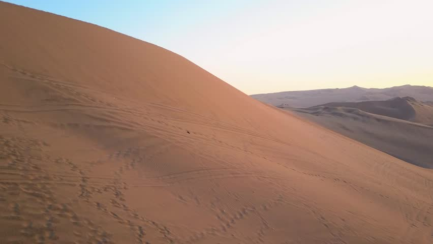 Aerial drone footage on a sunny day above sand dunes of Peru. Close to Ica and Huacachina. Similar to Sahara and Emirates Deserts. Boogie cars driving and people sandboarding. Color Corrected.   Shutterstock HD Video #30910558