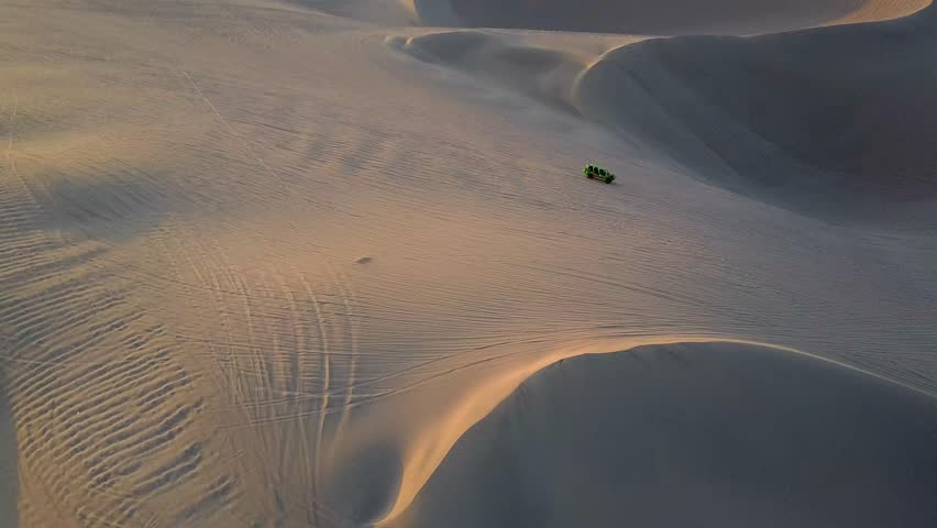 Aerial drone footage on a sunny day above sand dunes of Peru. Close to Ica and Huacachina. Similar to Sahara and Emirates Deserts. Boogie cars driving and people sandboarding. Color Corrected.   Shutterstock HD Video #30910576