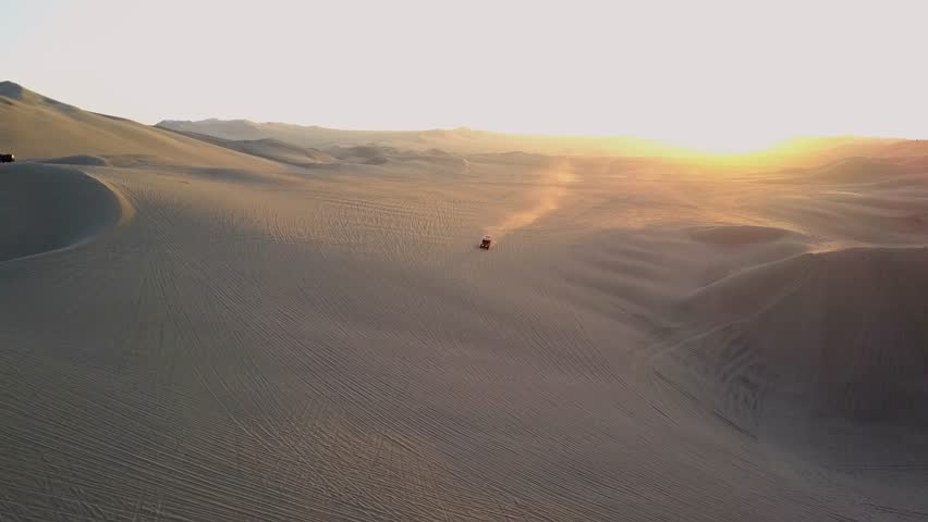 Aerial drone footage on a sunny day above sand dunes of Peru. Close to Ica and Huacachina. Similar to Sahara and Emirates Deserts. Boogie cars driving and people sandboarding. Color Corrected.   Shutterstock HD Video #30910585