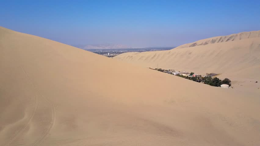 Flying on a drone on a sunny day above sand dunes of Peru. Close to Ica and Huacachina. Similar to Sahara and Emirates Deserts. Boogie cars driving and people sandboarding. Color Corrected.   Shutterstock HD Video #30910795