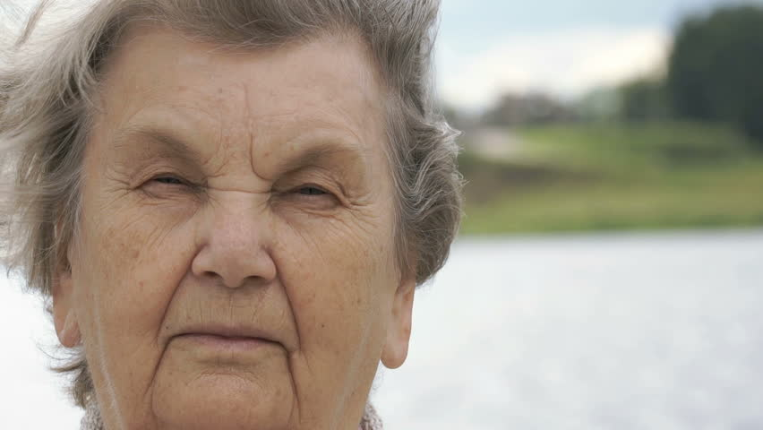 Portrait of serious mature old woman with gray hair on the background of river in summer. Slow Motion #30916993