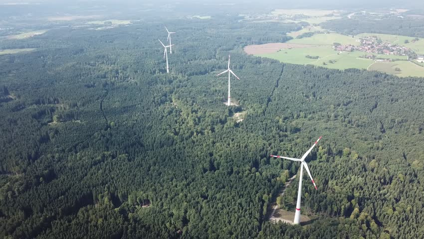 Windmills producing electricity placed in forest #30924880