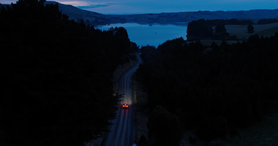 Aerial view car driving on country road at dusk through forest with headlights | Shutterstock HD Video #30940000