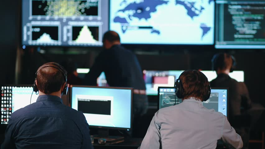 A team of security personnel working in a busy system control room, could be a weather station airport traffic control. It could be a power station or police army control facility.