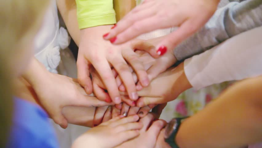 Many children connect they hands and adult hands lies superiorly during team gathering #3095815