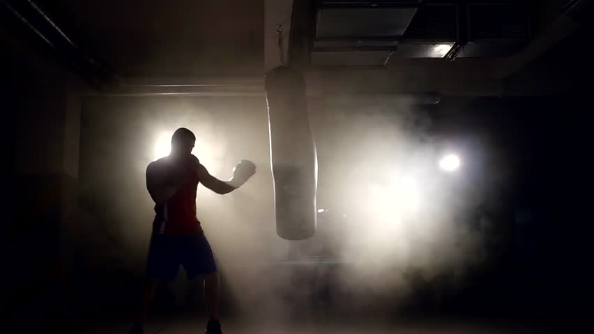 Alone large boxer is working out blows on a punching bag in a dark gym