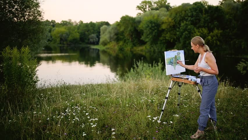 Young artist painting picture in park with brushes and colors sitting by the romantic lake and urban buildings in background. ultra wide angle view | Shutterstock HD Video #30962203