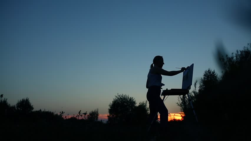 Silhouette of a girl. The blonde girl paints a painting on the canvas with the help of paints