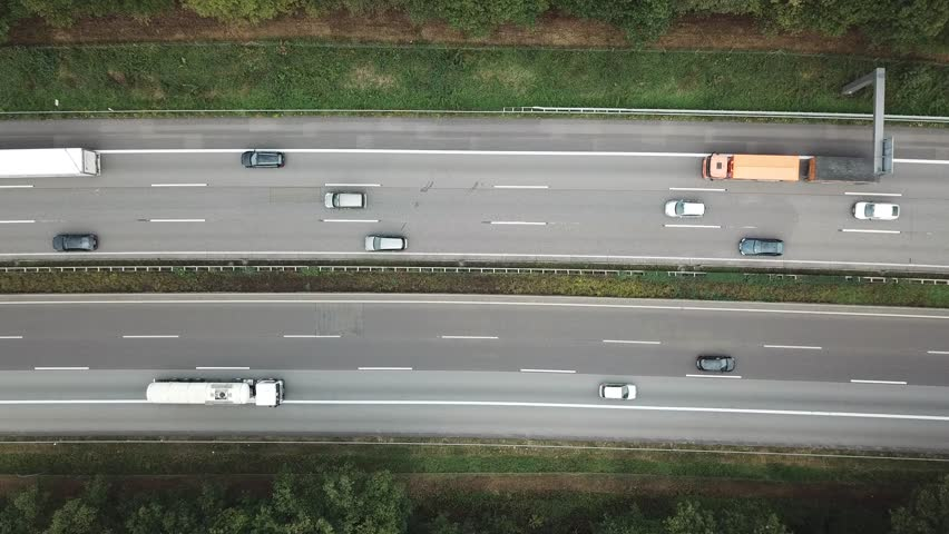 Aerial view of a highway in Germany. Traffic jam in one direction. Lots of trucks and small cars stuck in slow traffic.