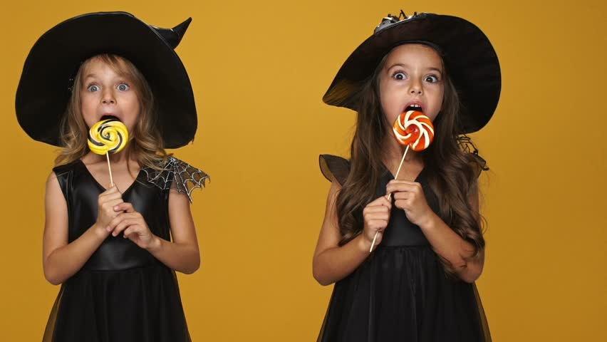 Little pretty girls witches in decorated dresses and hats eating lollipops isolated over orange