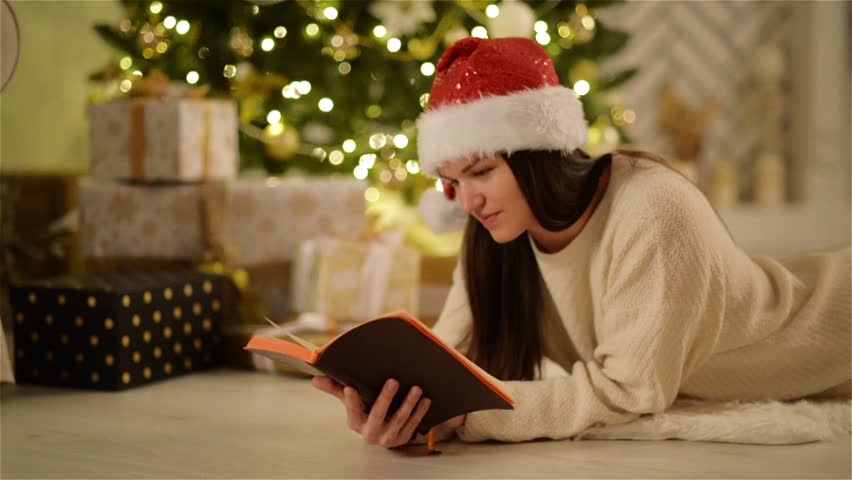 Happy Amazed Woman in Santa Hat with Long Hair Laying on the Floor and Enjoying Reading. Closeup Portrait of Smiling Girl Holding an Opened Book in Hands Next to Christmas Tree and Boxes with Gifts. | Shutterstock HD Video #30970225