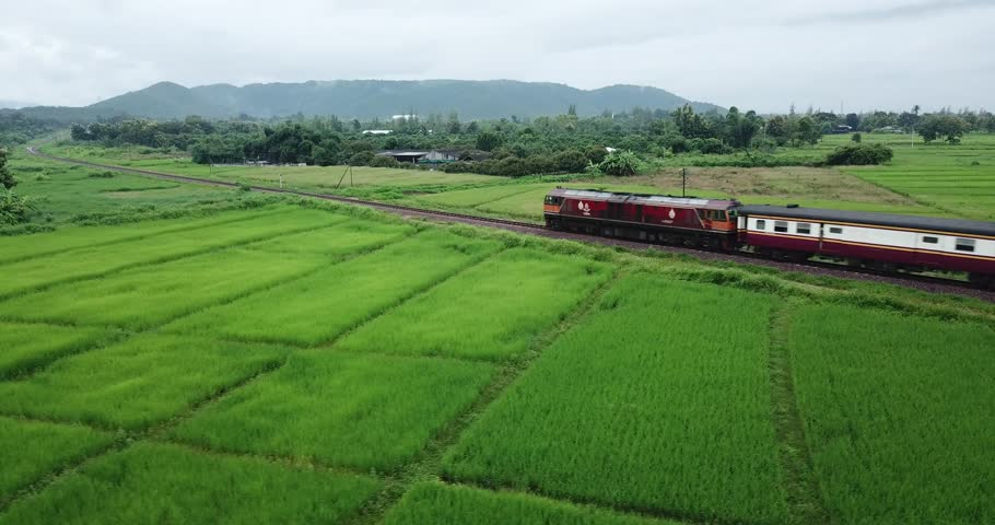 Train through paddy fields Heading into the valley in northern Thailand.The Utravithi train is the newest train set in Thailand. | Shutterstock HD Video #30972400