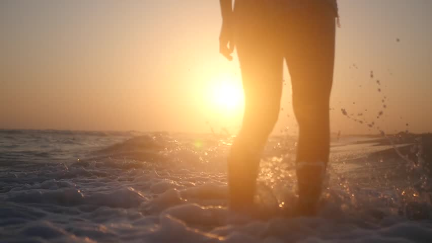 Go along the seashore to the sunset on the waves with splashes. Slow Motion. Closeup. HD, 1920x1080. #30978685