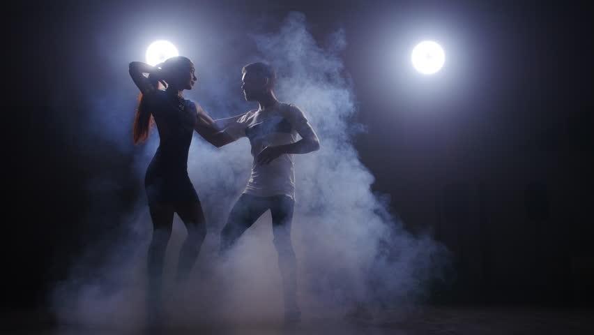 Beauty couple dancing bachata in dark room