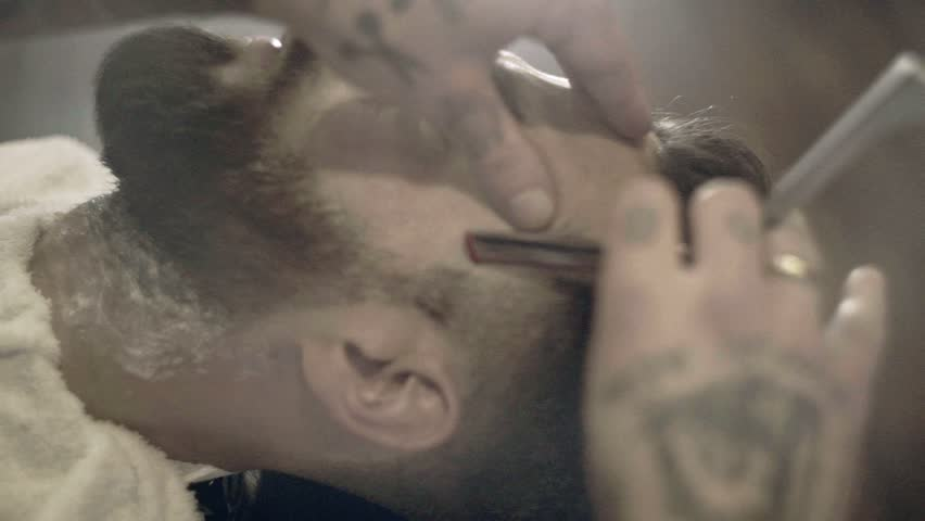 Beard cut with straight razor shave. Close up of shaving beard in barber shop. Male beard style. Barber shaving hipster man face