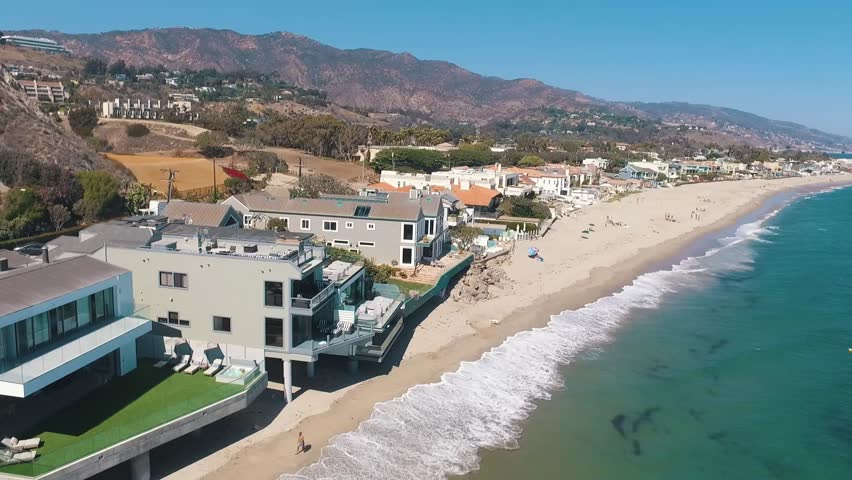 Aerial drone over beachfront homes and ocean in Malibu, California.