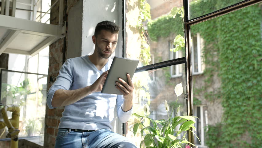 Handsome man in blue sweater looks shocked while reading news on the internet, steadycam shot  | Shutterstock HD Video #30992308